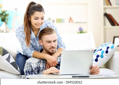 Happy couple sitting at the table and working with a laptop