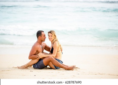 Happy couple sitting together on sand and smiling