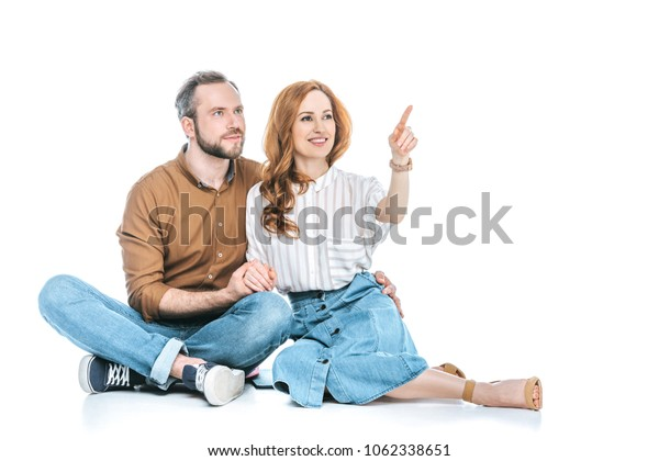 happy couple sitting together and pointing away with finger isolated on white