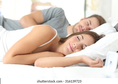 Happy couple sleeping in a comfortable bed at home