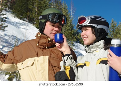 Happy couple snowboarders drinking hot tee