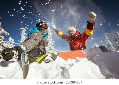 Happy couple of snowboarders having fun sitting in snowdrift with snowboards and  tossing snow