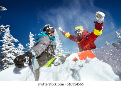 Happy couple of snowboarders having fun tossing snow and smiling