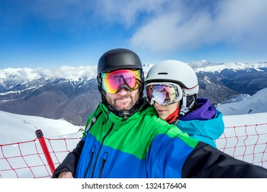 Happy couple snowboarders standing on edge of mountain peaks and taking selfie portrait with camera or smartphone on  background of snowy mountains in ski resort