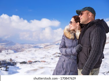 Happy couple in snowing mountains, active lifestyle, winter vacation, luxury wintertime resort, loving family, cold weather
