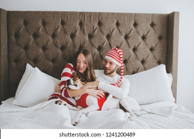 Happy couple snuggled with dog on bed in Christmas holiday clothing