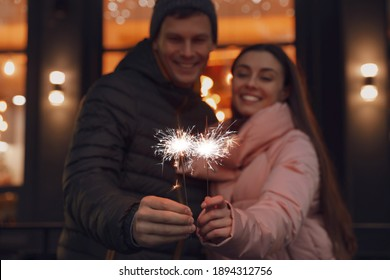 Happy couple with sparklers at winter fair