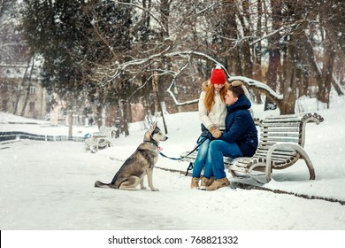 Happy couple is spending their time with siberian dog in the snowy park during the snowfall. The charming red head girl is sitting on the laps of her boyfriend.