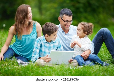 Happy couple spending time in the park with their children