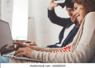 Happy couple spending time together with electronic devices. Man playing computer game with VR googles. Woman using laptop