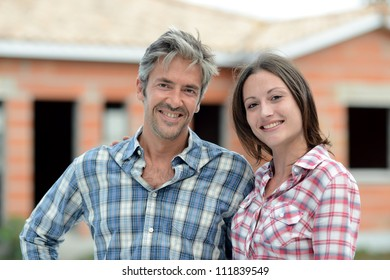 Happy couple standing in front of house under construction