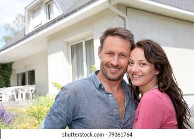 Happy couple standing in front of new home