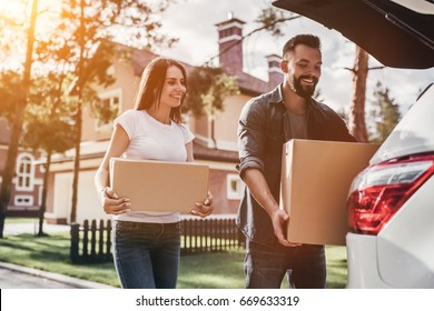 Happy couple is standing near car with cardboard boxes. Moving day.