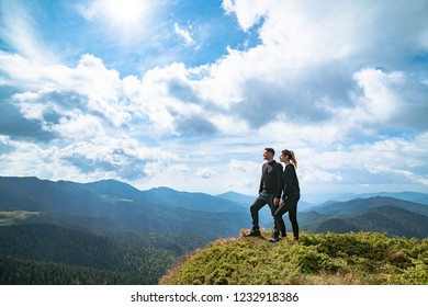 The happy couple standing on the mountain with a picturesque cloudscape