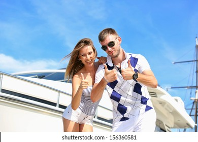 Happy couple standing on the pier in the background of the yacht