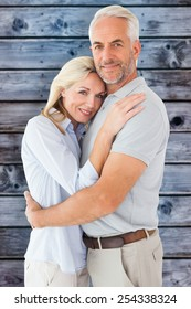 Happy couple standing and smiling at camera against wooden background in blue