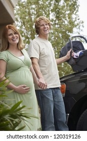 Happy couple standing together with baby carrier by car