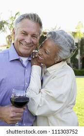 Happy couple standing together while man holding wine glass
