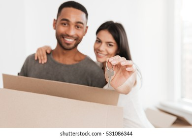 Happy couple standing with unpacked boxes. Woman hugging man. Man holding box and key. Looking at camera. Focus on key.