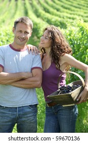 Happy couple standing in vineyard