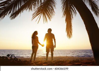 Happy couple stands on a beach under palm tree on sunset sea background
