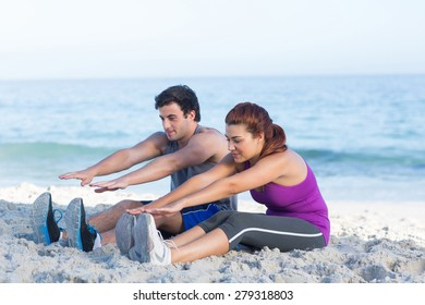 Happy couple stretching together beside the water at the beach