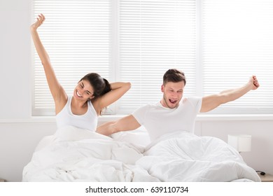 Happy Couple Stretching While Waking Up At Morning On Bed