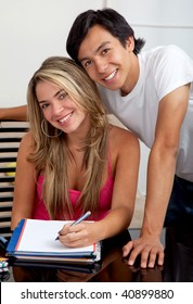 Happy couple of students at home with notebooks