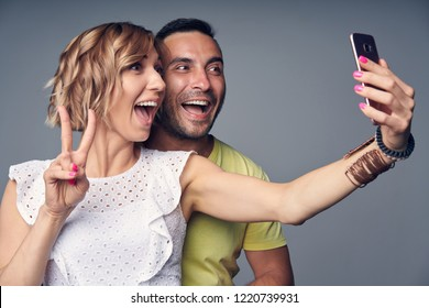 Happy couple in studio having fun making self portrait on smart phone gesturing V sign and making funny face, over grey background