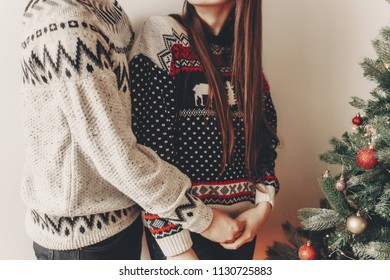 happy couple in stylish sweaters decorating christmas tree. merry christmas and happy new year concept. space for text. woman and man hugging. family cozy moments