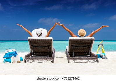Happy couple in sunbeds enjoys their vacation on a tropical beach with turquoise waters