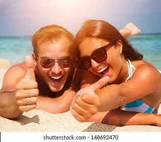 Happy Couple in Sunglasses having fun on the Beach. Summer Vacation. Laughing Family enjoying Nature over Sea Background. Attractive Man and Woman at the Beach