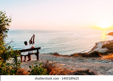 Happy couple at sunset. Man and woman at dawn. Couple sitting on a bench by the sea. Couple in love kissing by the sea. Man and woman traveling. Honeymoon trip. Sunset on sea. Dawn by the sea