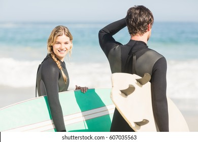 Happy couple with surfboard standing on the beach on a sunny day