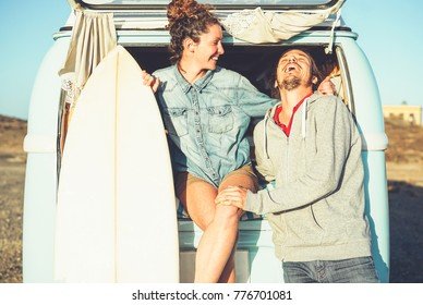 Happy couple of surfers standing behind on vintage camper van - Young people adventuring on road trip with a minivan transport - Concept of travel, hippie, lifestyle