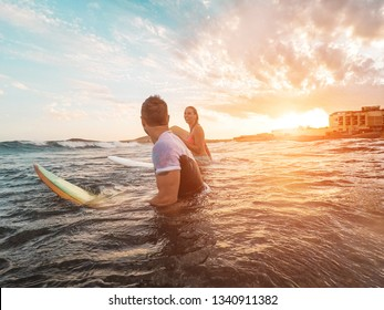 Happy couple surfing at sunset - Surfers friends having fun inside ocean - Extreme sport and sumer vacation concept - Focus on man head - Sun colors filter tones
