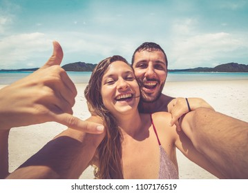 Happy couple take selfie on the beautiful beach in the Whitsunday Islands in Australia