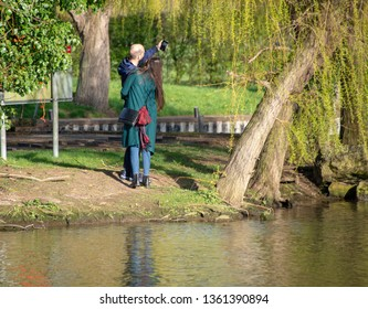 happy couple take selfy on vacation in the UK by the side of a river with canal in the background