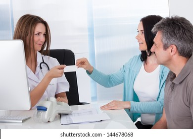 Happy Couple Taking Giving Card From Doctor