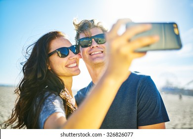 happy couple taking romantic selfie on beach with bright sun with lens flare and selective focus