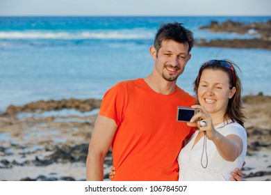 Happy couple taking a self portrait with a camera