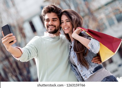 Happy couple taking selfie after shopping in the city. Couple enjoying in moments of happiness.