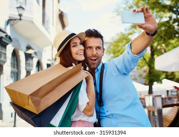 Happy couple taking selfie after shopping in the city