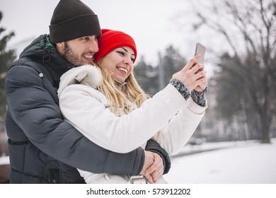 Happy couple taking selfie by smartp hone in winter