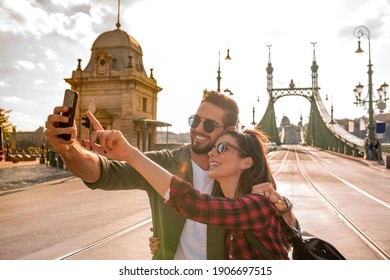 A happy couple taking a selfie in front of the famous liberty bridge during summer in Budapest in Hungary..