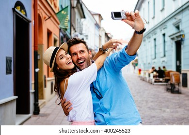 Happy couple taking selfie on the street during Europe vacation