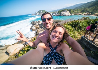 happy couple taking selfie photo in front of the sea in Tayrona National Park, Tropical Colombia. Crazy tourists travelling on the white beach of caribbean sea.