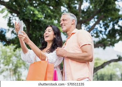 Happy couple taking selfie from smartphone with shopping bags in city