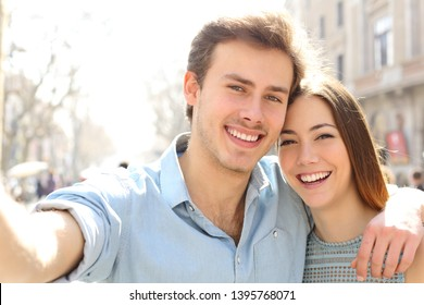 Happy couple are taking selfies in the street on summer holiday in a big city