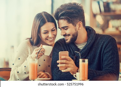 Happy couple taking a selfie.They are enjoying sitting in cafe.